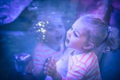 Muchacha emocionada del niño hermoso Surprised que mira con la admiración a través del vidrio del acuario en ama púrpura azul de  imagen de archivo