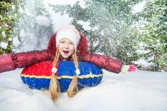 Muchacha emocionada en el tubo de la nieve en invierno durante día Imagen de archivo libre de regalías