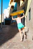 Muchacha emocionada muy feliz que va a casa con la tabla hawaiana de la playa Imagen de archivo libre de regalías