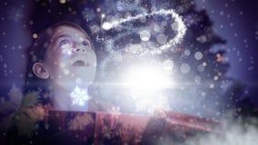 Muchacha emocionada que abre la caja de regalo mágica de la Navidad con la luz chispeante almacen de metraje de vídeo