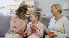 Muchacha emocionada que dice la mamá y a la abuelita historia divertida sobre la escuela, confiando en relaciones metrajes