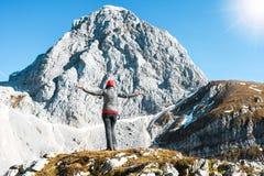 Muchacha emocionada que ejercita con el sombrero anaranjado que mira a un pico de montaña en un día soleado agradable del otoño foto de archivo