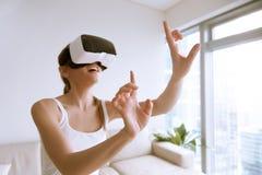 Muchacha emocionada que lleva los vidrios de VR que tocan objetos en worl virtual Foto de archivo libre de regalías