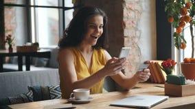 Muchacha emocionada que paga en línea con la tarjeta del smartphone y de crédito que se sienta en café solamente metrajes