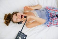 Muchacha emocionada que pone en cama y el teléfono de discurso Fotografía de archivo