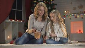 Muchacha emocionada que pone la letra para Papá Noel en sobre y que abraza a la mamá, víspera de Navidad metrajes