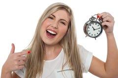 Muchacha emocionada que sostiene el reloj de alarma pasado de moda Imagen de archivo