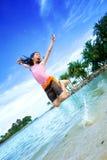Muchacha emocionada, saltando en la playa de la laguna foto de archivo
