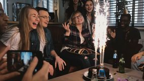 Muchacha emocional del cumpleaños que agradece a los amigos multiétnicos felices por fiesta de cumpleaños asombrosa con la cámara almacen de video