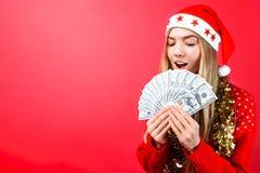 Muchacha emocional en un suéter y un sombrero rojos de Santa Claus, en la admiración que sostiene el dinero en un fondo rojo foto de archivo