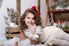 Muchacha emocional hermosa En un estudio casero por el Año Nuevo y la Navidad En un vestido blanco con un arco rojo y los calceti Imagen de archivo libre de regalías