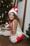Muchacha emocional hermosa En un estudio casero por el Año Nuevo y la Navidad En un vestido blanco con un arco rojo y los calceti Fotos de archivo