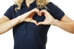 Muchacha emocional joven hermosa que muestra el corazón de las manos en un fondo aislado El concepto de amor y de salud imágenes de archivo libres de regalías