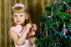 Muchacha en árbol de navidad adornado rosado Imagenes de archivo