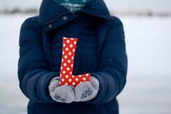 Muchacha en abajo chaqueta azul y guantes que llevan a cabo una letra del tejido Foto de archivo libre de regalías