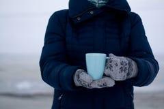 Muchacha en abajo chaqueta azul y guantes que sostienen una taza de té Fotos de archivo