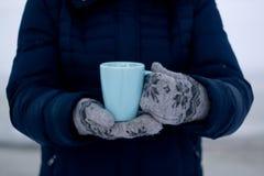 Muchacha en abajo chaqueta azul y guantes que sostienen una taza de té Imágenes de archivo libres de regalías