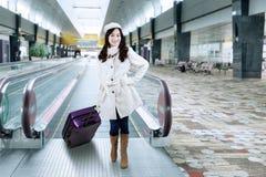 Muchacha en abrigo de invierno en el vestíbulo del aeropuerto Fotos de archivo libres de regalías