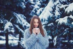 Muchacha en abrigo de pieles con una taza Fotos de archivo