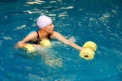 Muchacha en agua con los dumbbels Foto de archivo