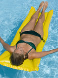 Muchacha en airbed en una piscina imagenes de archivo