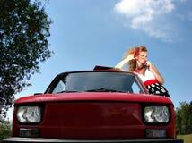 Muchacha en alineada con el coche rojo del comapct foto de archivo libre de regalías