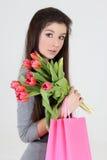 Muchacha en alineada con los bolsos y las flores de compras Imagen de archivo libre de regalías