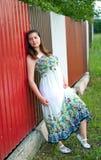 Muchacha en alineada ligera contra la cerca del metal Foto de archivo