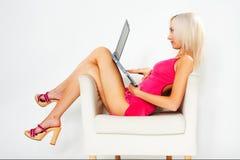 Muchacha en alineada rosada con la computadora portátil Fotografía de archivo libre de regalías