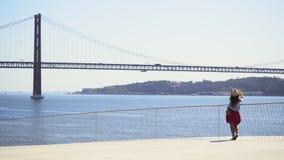 Muchacha en alto punto de visión sobre la costa en Lisboa almacen de metraje de vídeo