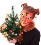 Muchacha en aspecto un tigre con un árbol del nuevo-año. Foto de archivo