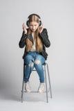 Muchacha en auriculares atados con alambre se está sentando y que escucha música Foto de archivo