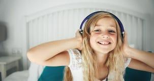 Muchacha en auriculares en la cama que se divierte almacen de video