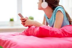 Muchacha en auriculares que escucha la música en casa Imagen de archivo