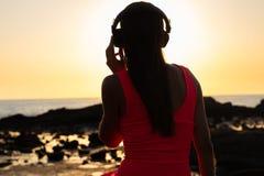 Muchacha en auriculares que escucha la música en la ciudad en la puesta del sol imagen de archivo libre de regalías