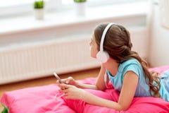 Muchacha en auriculares que escucha la música en casa Foto de archivo
