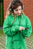 Muchacha en auriculares que escucha la música en el teléfono móvil Foto de archivo libre de regalías