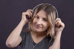 Muchacha en auriculares que escucha la música y que disfruta de la sonrisa fotos de archivo libres de regalías