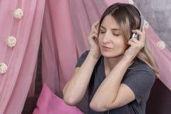 Muchacha en auriculares que escucha la m?sica y que disfruta de la sonrisa fotos de archivo