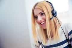 Muchacha en auriculares usando el equipo de escritorio Fotos de archivo libres de regalías