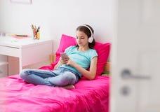 Muchacha en auriculares y smartphone en casa Imágenes de archivo libres de regalías
