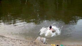 Muchacha en bañador rosado con funcionamientos largos del pelo abajo de la playa y zambullidas en el agua que salpica descensos F almacen de metraje de vídeo