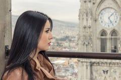 Muchacha en balcón con la opinión de la ciudad detrás de ella Imagenes de archivo
