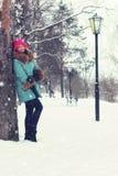 Muchacha en banco de la calle del invierno Imágenes de archivo libres de regalías