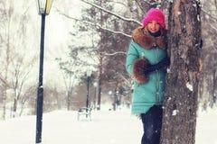Muchacha en banco de la calle del invierno Fotografía de archivo