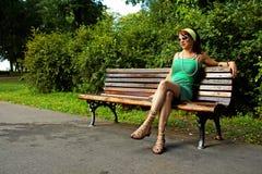 Muchacha en banco de parque Fotografía de archivo