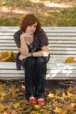 Muchacha en banco de parque del otoño Imagen de archivo