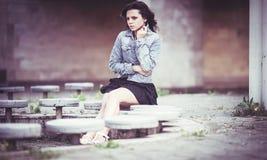 Muchacha en banco en chaqueta del dril de algodón Fotografía de archivo libre de regalías