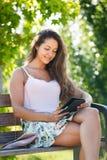 Muchacha en banco en parque con el ereader Foto de archivo libre de regalías