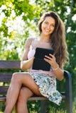 Muchacha en banco en parque con el ereader Imagenes de archivo